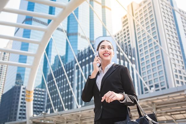 Giovane donna moderna di affari che per mezzo dello smart phone con lo spazio della copia