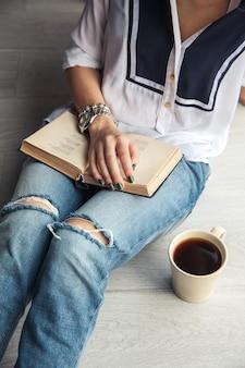 Giovane ragazza moderna in jeans strappati leggendo un libro con una grande tazza di caffè.