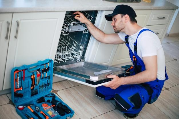 Giovane militare moderno in tuta da lavoratore durante la riparazione della lavastoviglie sulla cucina domestica.