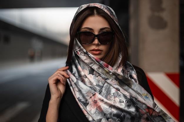 Modello di moda giovane donna urbana moderna in elegante scialle alla moda in occhiali da sole in cappotto nero in posa in città per strada. ragazza alla moda di affari del ritratto all'aperto. abiti da donna di eleganza.