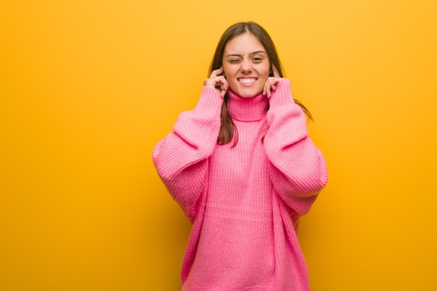 Giovane donna moderna che copre le orecchie con le mani