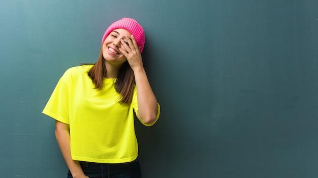 Giovane donna moderna imbarazzata e ridente allo stesso tempo