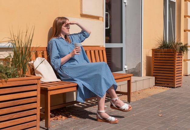 Giovane donna moderna in abito sciolto che riposa con una tazza di caffè eco riutilizzabile sulla strada della città in estate e ...