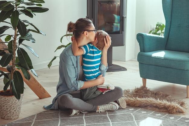 Giovane mamma e bambino che si abbracciano seduti sul pavimento a casa