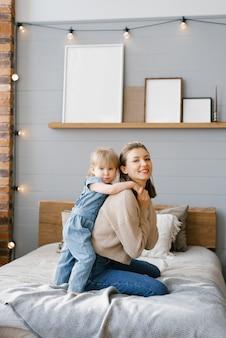 La giovane mamma si coccola con la figlia di due anni sul letto
