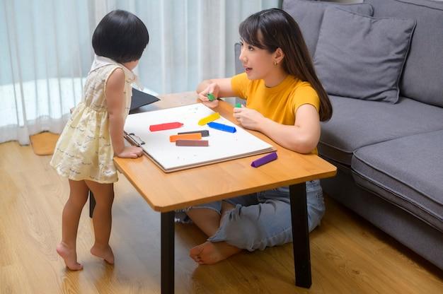 Una giovane mamma che aiuta la figlia a disegnare con matite colorate nel soggiorno di casa.