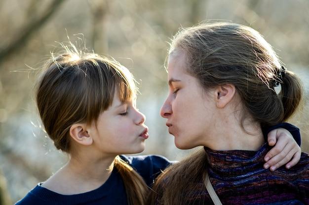 Giovane mamma e sua figlia insieme all'aperto Foto Premium
