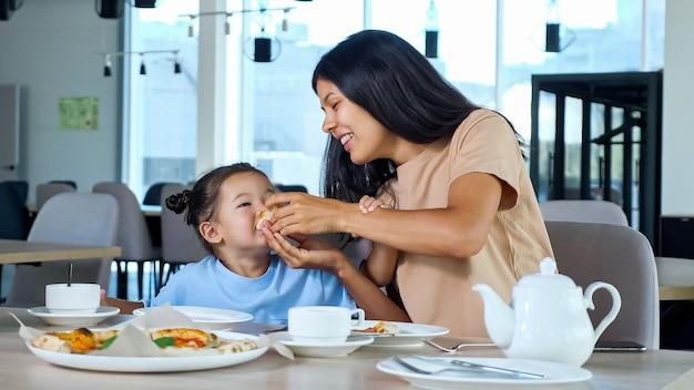 La giovane mamma tiene in mano una fetta di pizza e la bambina mangia giocando