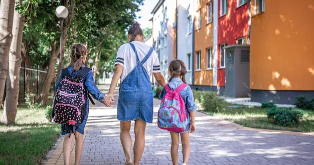 La giovane mamma è accompagnata dalle bambine a scuola, vista posteriore.