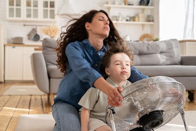 La giovane mamma e il bambino siedono con gli occhi chiusi davanti al ventilatore in soggiorno e si godono il soffio d'aria fresca