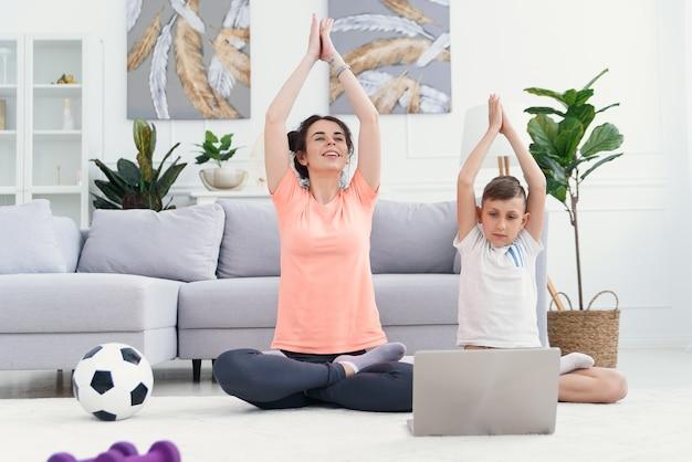 Giovane mamma e figlio praticano yoga con il computer portatile di fronte a loro