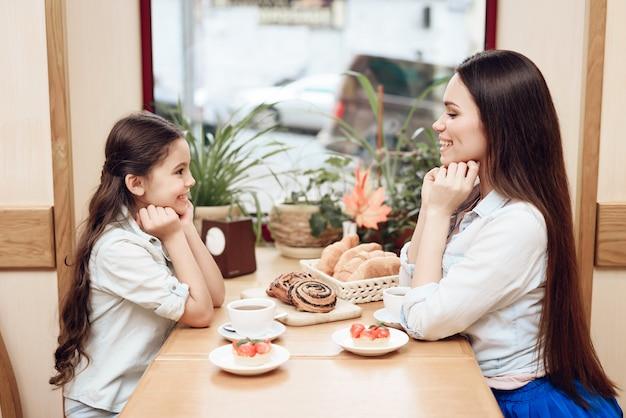 Giovane mamma con figlia mangiare torte in caffetteria.