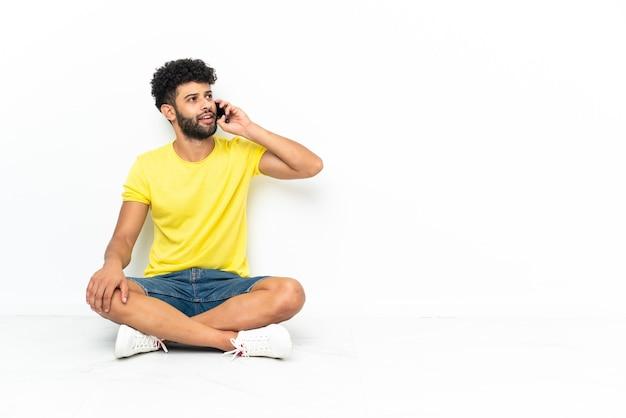 Giovane marocchino uomo bello seduto sul pavimento su sfondo isolato mantenendo una conversazione con il telefono cellulare