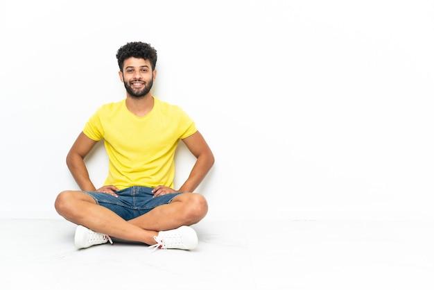 Giovane uomo bello marocchino seduto sul pavimento su sfondo isolato ridendo