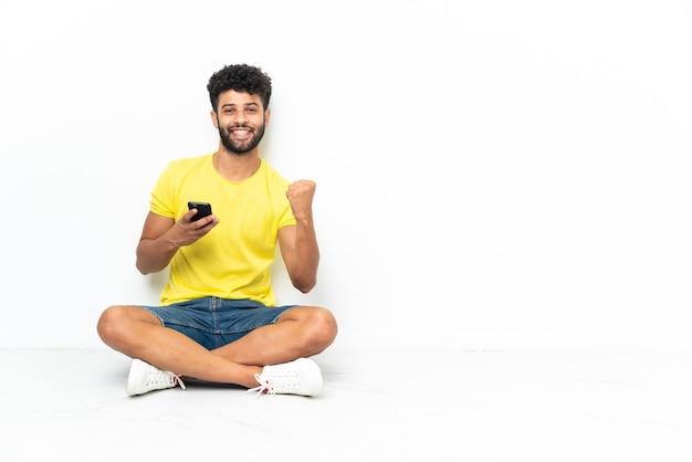 Giovane uomo bello marocchino seduto sul pavimento su sfondo isolato con il telefono in posizione di vittoria