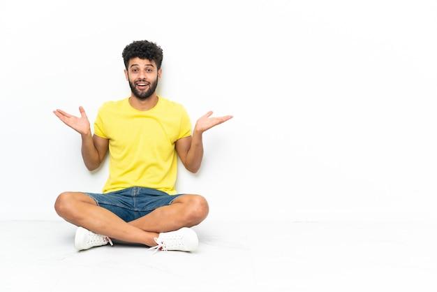 Giovane uomo bello marocchino che si siede sul pavimento sopra la parete isolata con l'espressione facciale scioccata