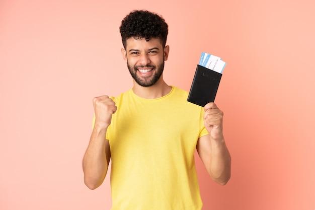 Giovane uomo marocchino isolato sulla parete rosa felice in vacanza con passaporto e biglietti aerei