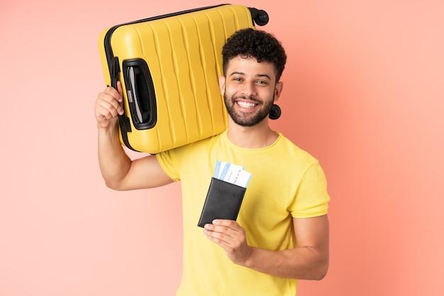 Giovane uomo marocchino isolato sulla parete rosa in vacanza con la valigia e il passaporto