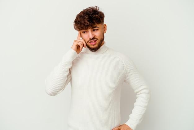 Giovane uomo marocchino isolato sul muro bianco che copre le orecchie con le mani.