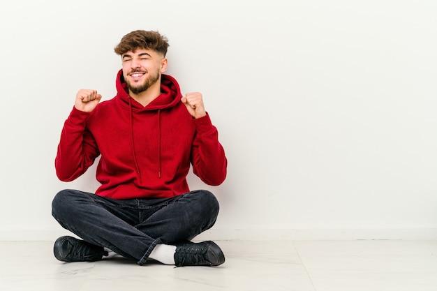 Giovane uomo marocchino seduto sul pavimento isolato su bianco che celebra una vittoria, passione ed entusiasmo, felice espressione.