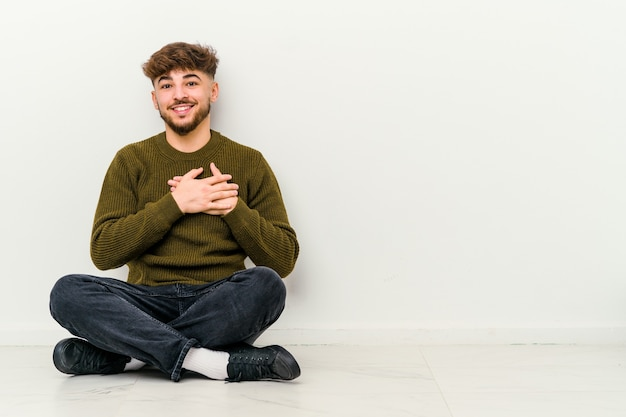 Il giovane marocchino seduto sul pavimento isolato su bianco ha un'espressione amichevole, premendo il palmo sul petto
