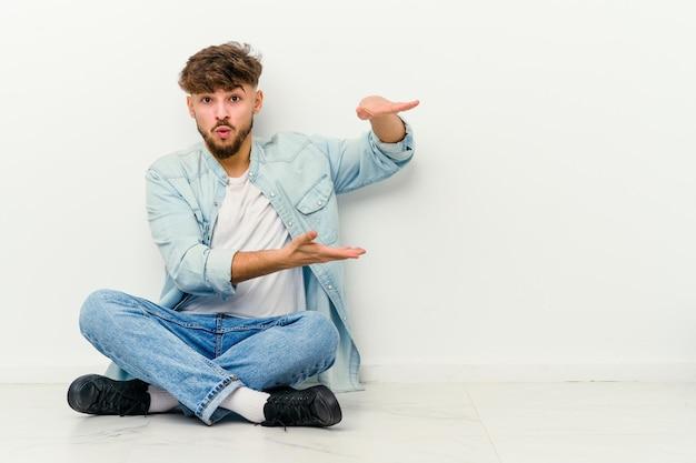 Giovane uomo marocchino seduto sul pavimento isolato su bianco tenendo qualcosa con entrambe le mani, presentazione del prodotto.