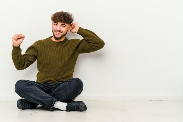 Giovane uomo marocchino seduto sul pavimento isolato sul muro bianco ballando e divertendosi.