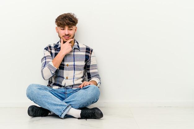 Giovane uomo marocchino seduto sul pavimento che tocca la parte posteriore della testa, pensando e facendo una scelta.