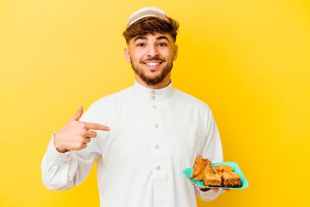 Giovane uomo marocchino che indossa il tipico costume arabo mangiare dolci arabi isolati su sfondo giallo persona che punta a mano a una copia spazio camicia, orgoglioso e fiducioso