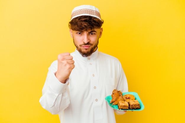 Giovane uomo marocchino che indossa il tipico costume arabo mangiare dolci arabi isolati su sfondo giallo che mostra il pugno alla telecamera, aggressiva espressione facciale.