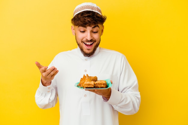 Giovane uomo marocchino che indossa il tipico costume arabo mangiare dolci arabi isolati su sfondo giallo