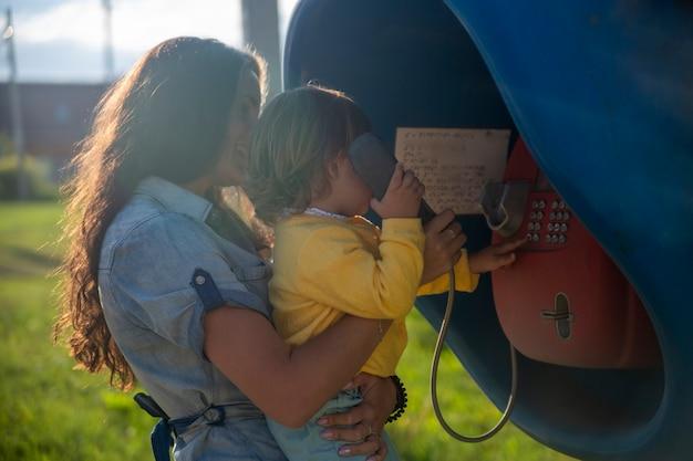 La giovane madre e il bambino chiamano su un telefono fisso su strada nella cabina telefonica del villaggio in estate. camminando con la famiglia giornata di sole estivo al sole. focus artistico