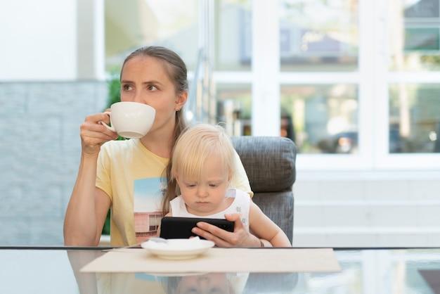 La giovane madre in caffè con il bambino beve il caffè e guarda il telefono. mamma d'affari moderna.