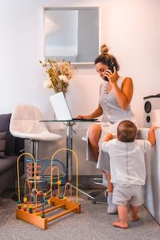 Giovane madre che si prende cura del suo giovane figlio e telelavoro da casa