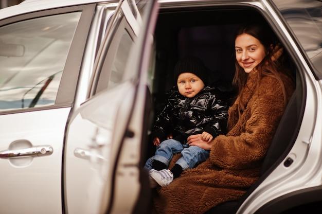 Giovane madre e figlio in auto. concetto di guida di sicurezza.