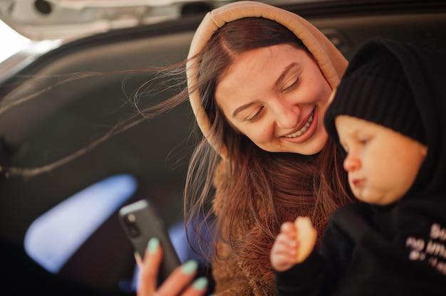 Giovane madre e bambino seduto nel bagagliaio di un'auto e guardando il telefono cellulare. concetto di guida di sicurezza.