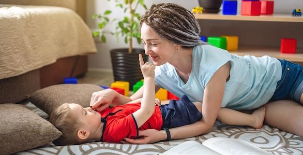 Una giovane madre e un bambino trascorrono del tempo insieme. si divertono, disegnano e giocano