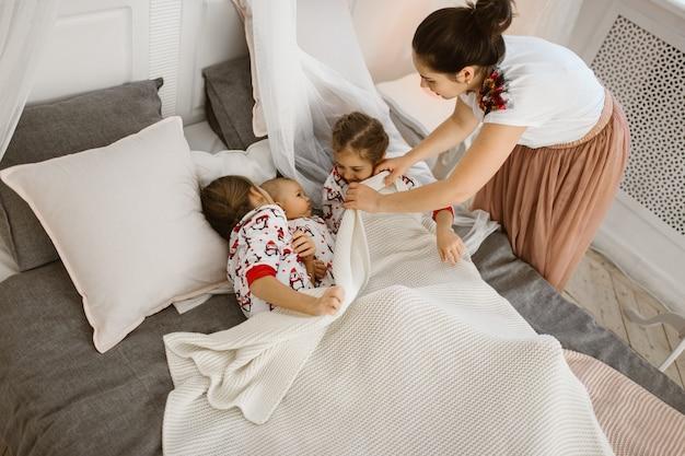 La giovane madre copre una coperta bianca per due figlie e un figlio piccolo che giacciono sul letto in una camera da letto luminosa e accogliente. .