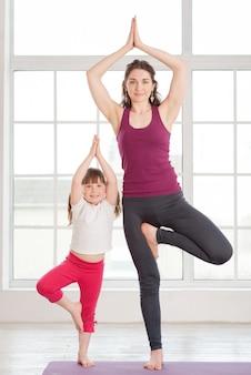 Giovane madre e figlia che fanno esercizio di yoga