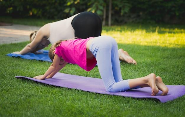 Giovane madre e figlia che praticano yoga sull'erba al park