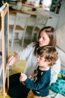 Giovane madre disegno gesso sulla lavagna con il suo giovane figlio a casa