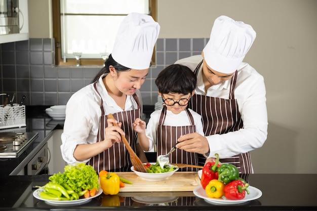 Giovane madre e padre con il figlio che cucinano insalata con verdure