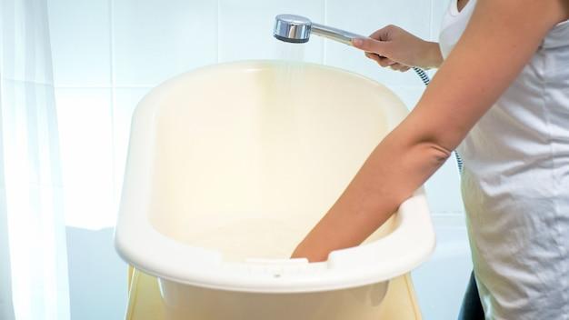 Giovane madre che riempie un piccolo bagno di plastica con acqua per lavare il bambino.