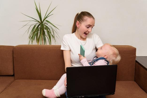 La giovane madre freelance sta giocando con il bambino e lavora con il laptop.