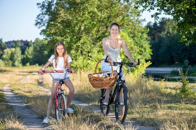 Giovane madre che va a fare un picnic con sua figlia in bicicletta