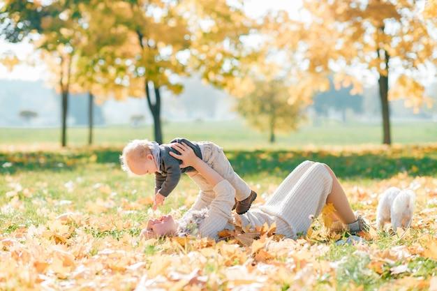 Giovane madre divertendosi con il suo bambino affascinante alla natura nel giorno soleggiato