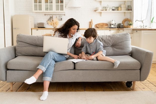 La giovane madre aiuta il figlio con i compiti durante la pausa dal lavoro sul computer portatile dal blocco della famiglia di casa