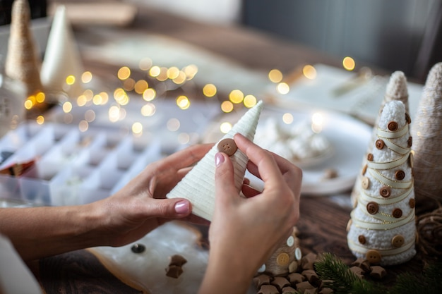 Giovane madre che aiuta la figlia ad avvolgere il cono di schiuma con spago o filo e realizzare alberi di natale di diverse dimensioni per la decorazione della tavola. concetto di preparazione per festività e feste.