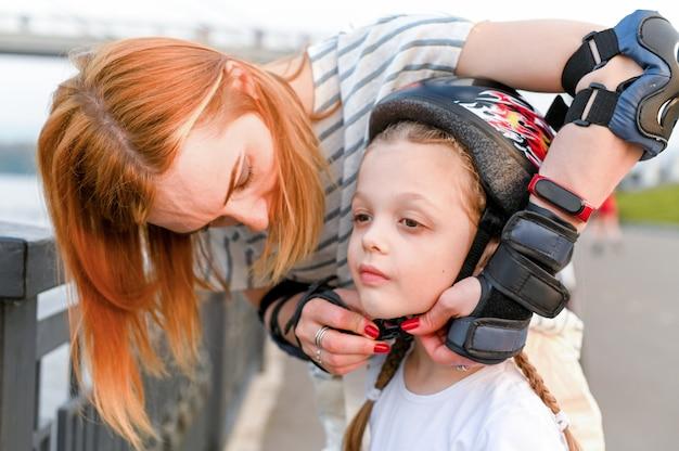 Giovane madre che aiuta la sua piccola figlia a mettere un casco da bicicletta. i bambini indossano elmetti di sicurezza mentre pattinano