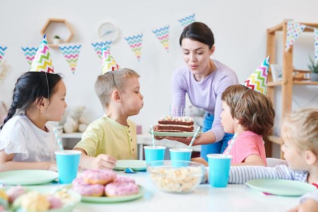 Giovane madre che aiuta i bambini piccoli a soffiare le candeline sulla torta di compleanno durante la festa a casa intorno al tavolo servito